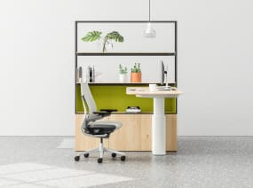 A Mackinac desk and Gesture desk chair shown next to a shelving unit in an individual workstation
