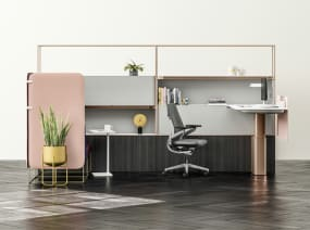A workstation featuring a Mackinac desk, Gesture desk chair with gray upholstery, and Umami lounge seating with attached privacy screens