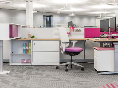 work area with gray carpet, white and purple office chair, height-adjustable desk with dual monitor on it.