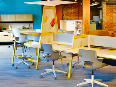 Work area with wooden desks, privacy screens, gray stools.