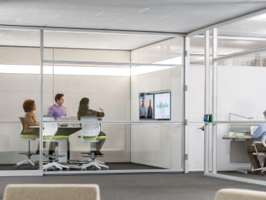 Three people collaborating inside a meeting room with glass walls while seated on green stools. A man working inside a room next to them.