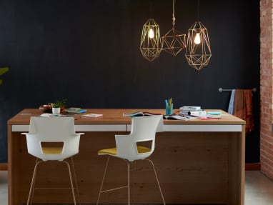 Collaborative office with a wooden Big table with magazine and notebook on it, two white stools