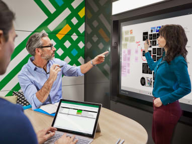 Man and woman on a private room collaborating while using an interactive ideation hub surface