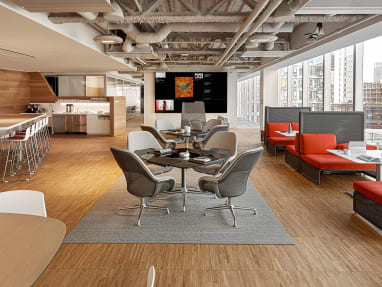 An office cafe setting features gray SW_1 lounge chairs, Lagunitas lounge seating with orange upholstery, and SW_1 tables