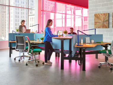 Three people work at a group of workstations created with Ology height adjustable desks, Gesture desk chairs, and Dash task lights