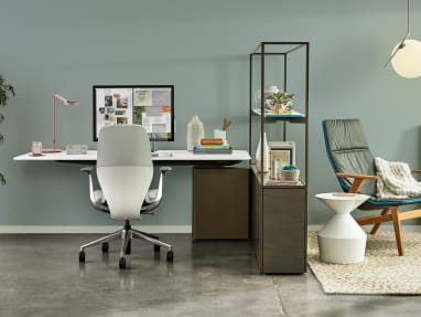 On the left side of the image, an individual workstation is created using a Steelcase Mackinac worksurface and a SILQ chair. The space is divided by a shelving unit with an armchair and table on the other side of the image.