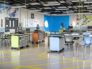 Education space with a variety of colorful products, that include chairs, desks and storage cabinets.