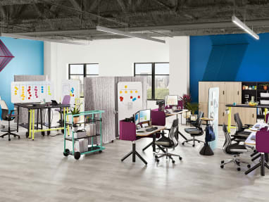 An office environment that includes Steelcase Flex height-adjustable desks, Gesture desk chairs, Flex Slim tables, SILQ stool height chairs, and Steelcase Flex carts