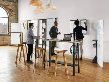 Three people gathered around a Steelcase Roam in a room with Flex standing-height tables and Enea cafe stools