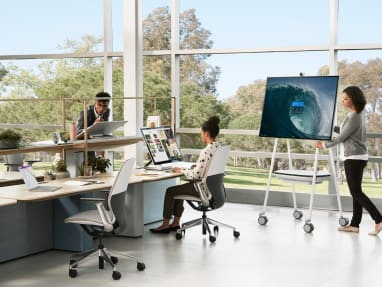 A woman moves a Steelcase Roam Mobile Stand near people working at Mackinac benches and SILQ desk chairs