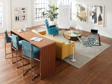 Open working sace featuring partner products including a standing height table, a colorful sofa and individual seats.