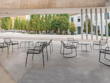 A variety of black EMU Rio R50 chairs and tables in an outdoor space.