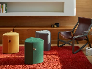 Ancillary space equipped with Turnstone Campfire Poufs in a variety of colors and a burgundy BluDot Toro Lounge Chair