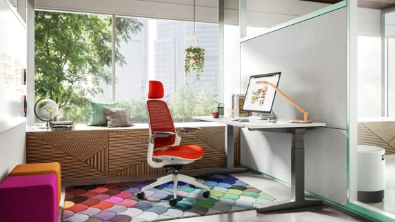 red Steelcase Series 1 with head rest inside a private room with white desk, Dash light on the desk and colorful rug.
