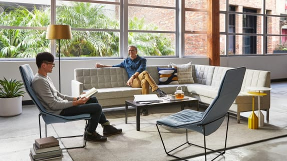 A man sits on a Millbrae Contact lounge sofa while talking to a man sitting on an Ace chair with a CG_1 table and Burin Tables from the Viccarbe Imports collection nearby