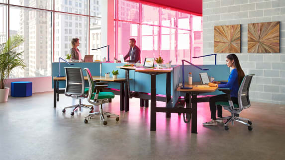 Three people work at a group of workstations created using Steelcase Ology benching and Gesture desk chairs