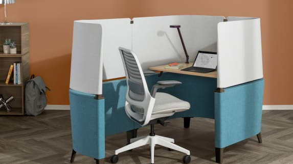 A light gray Steelcase Series 1 Chair stands in front of a blue Brody Desk.