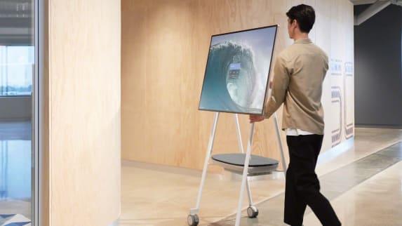 Man pushing a Steelcase Roam cart with Microsoft Surface Hub