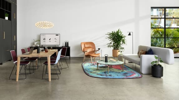 Ancillary setting with a variety of Partner products, that includes a gray Bolia Pebble Sofa, a white oak Bolia Graceful Dining Table, plum and white Nooi Seating, and a colorful Moooi rug.