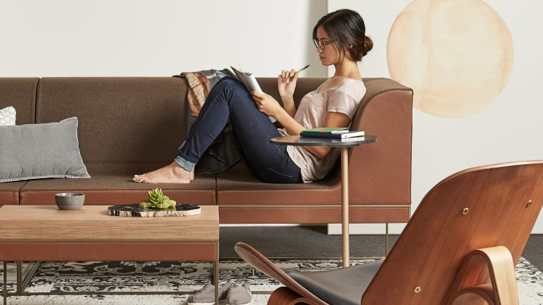 Woman writing on a notebook while seated on a brown Umami sofa with personal table