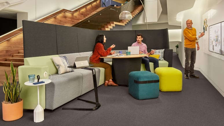 Three people work in a collaborative space in a workcafe furnished with partner products.