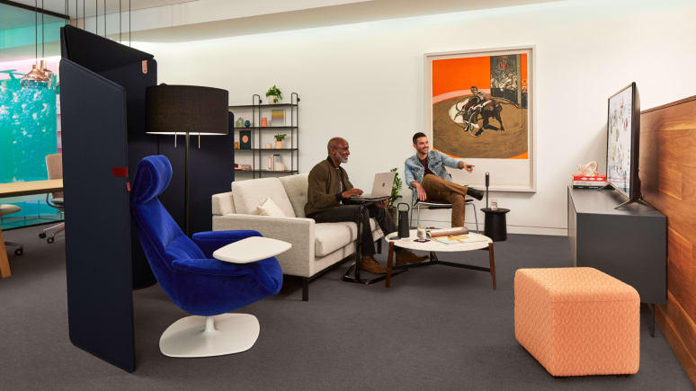 Two people engage with a TV screen in an open lounge space outfitted with partner products.
