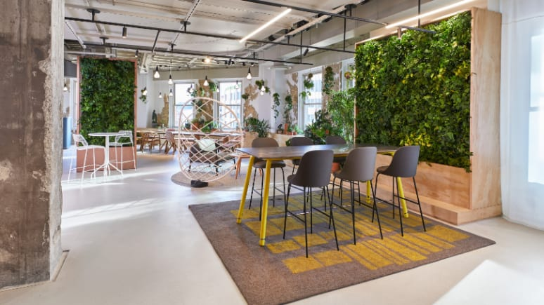 Stools from the Viccarbe collection are arranged around a Coalesse Potero415 table in front of a living plant wall from the Sagegreenlife collection