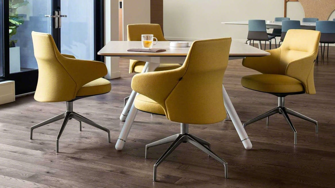 Four yellow Massaud low back chairs around a Potrero415 square table with an integrated PowerPod