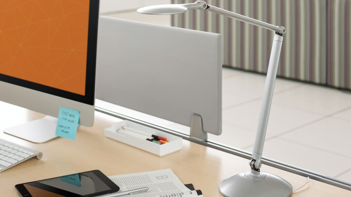 LED Radial Desktop light on a desk next to a magazine, a tablet and a monitor