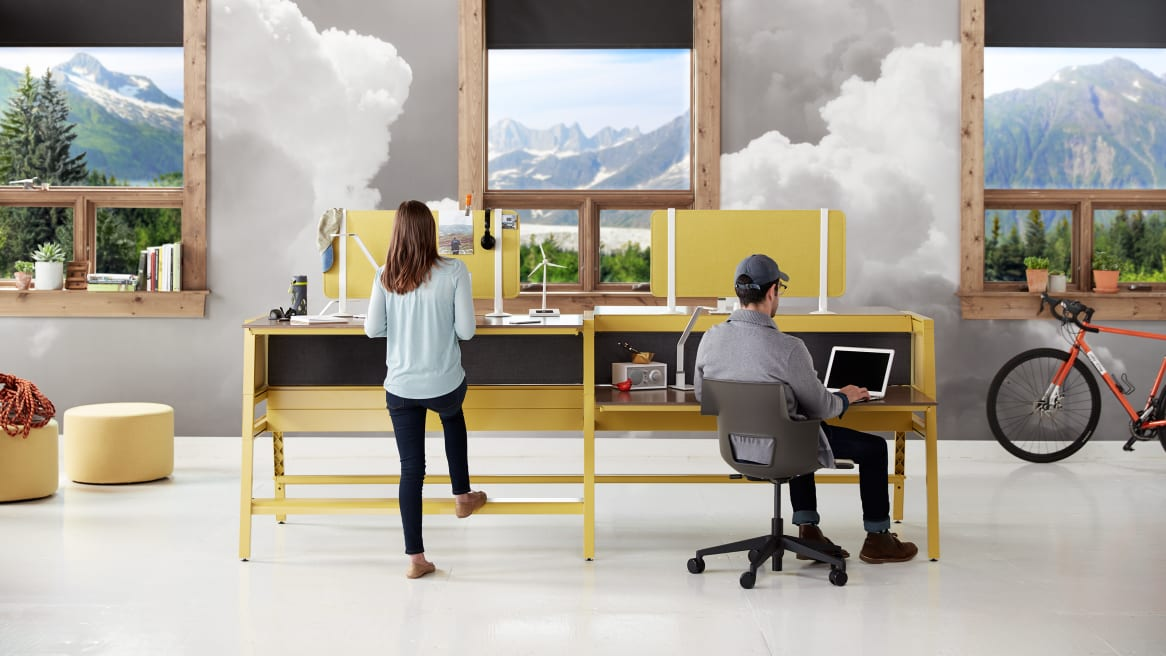 Two people work at a workstation of Bivi desks with yellow legs and privacy screens A woman uses a standing-height worksurface while a man sits in a gray Shortcut 5-Star base chair