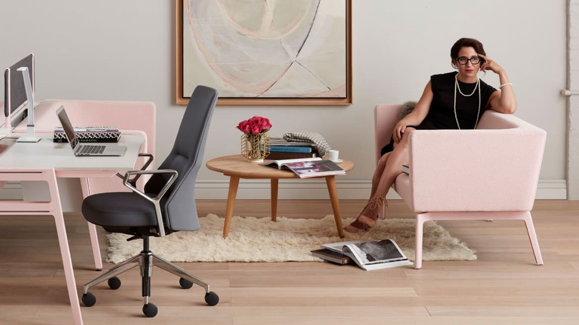 A woman sits on a Bivi Rumble Seat with pink upholstery next to a Bivi Table for Two with pink legs and Coalesse Massaud conference seating with gray upholstery