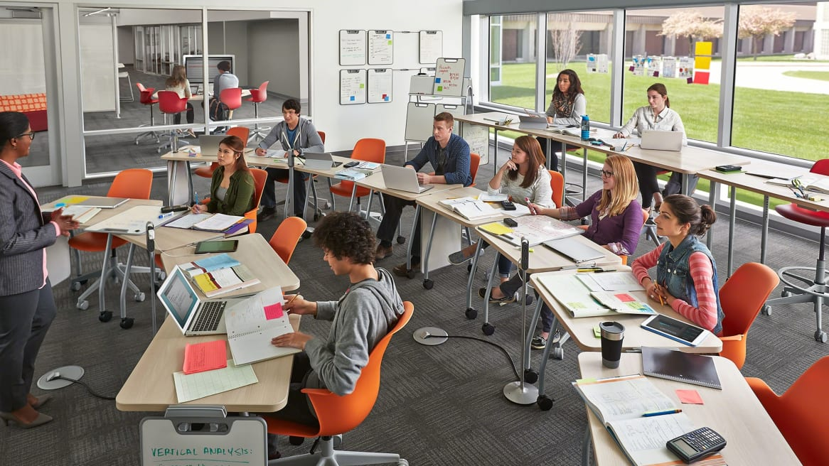 Classroom with Verb Tables with Light Wood Finish in a half-circle and Orange Node Chairs