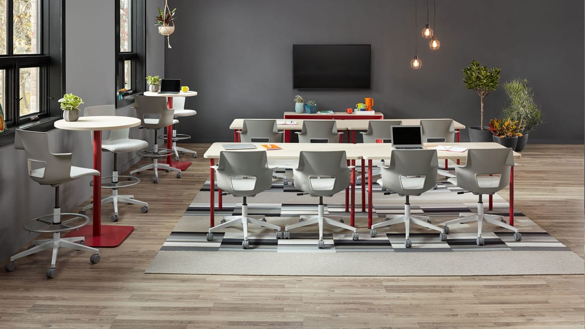 Four rectangular Simple Tables with red legs paired to form two long tables with white Shortcut office chairs and two round standing height Simple tables with red bases and accompanying Shortcut stools