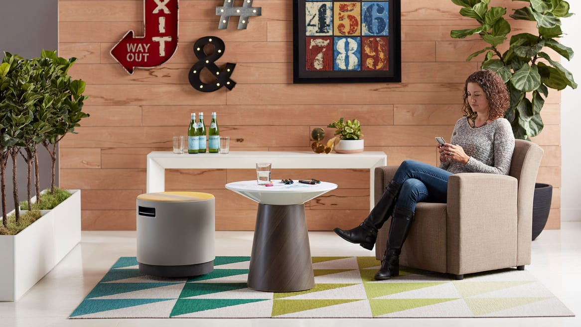 A woman sitting in a Jenny Low in an office lounge with a Campfire Paper Table, Campfire Slim Table, and a Buoy