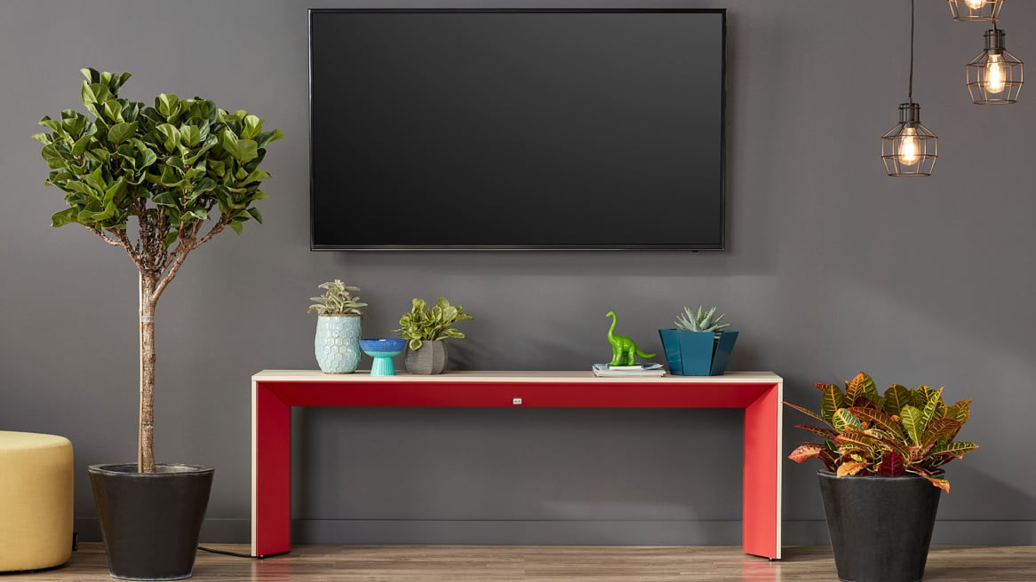 A red and white Campfire Slim Table against a wall under a TV