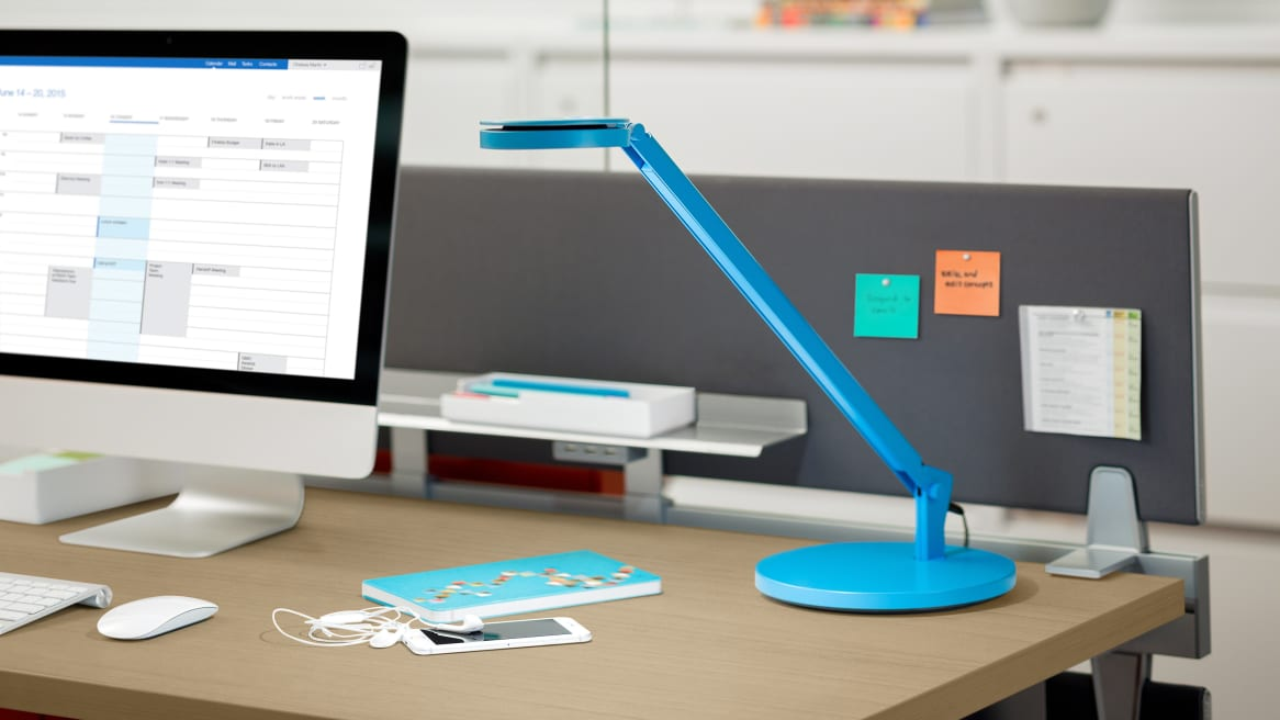 Blue Dash LED Mini Task Light on Desk next to a computer and a cellphone