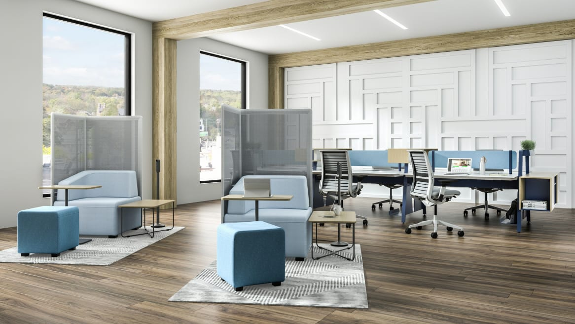 Open office with two light blue B-Free Big Cube Lounge Chairs and B-Free Cube Ottomans and B-Free Coffee Tables with a light wood finish