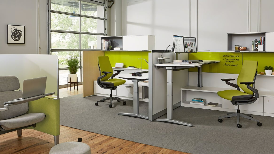 Ology desks with computers on it and green Gesture chairs