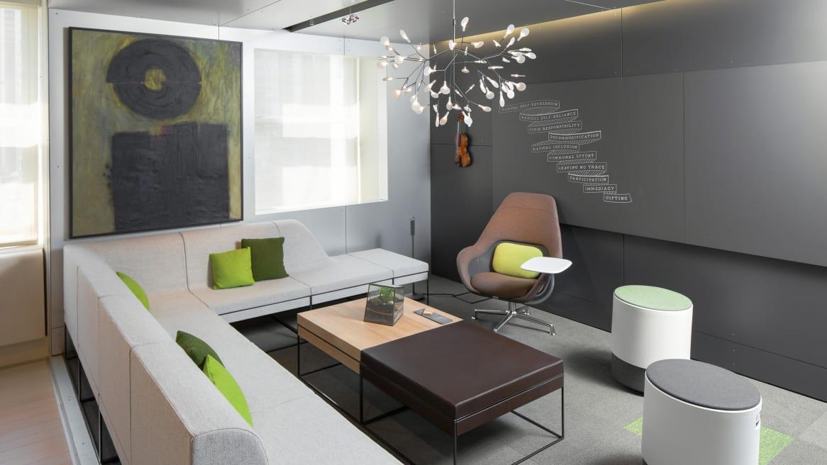 gray Umami sofa with green pillows, Sans dark boards on the wall, Buoy seats