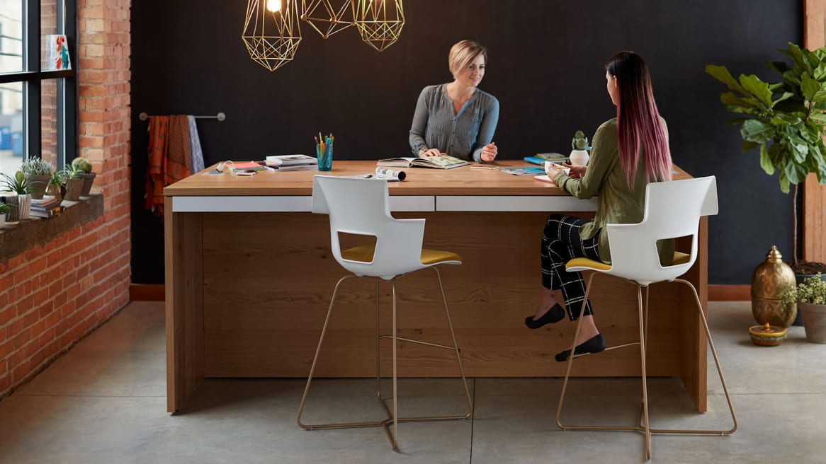 Woman sitting in Shortcut X Base stool at table