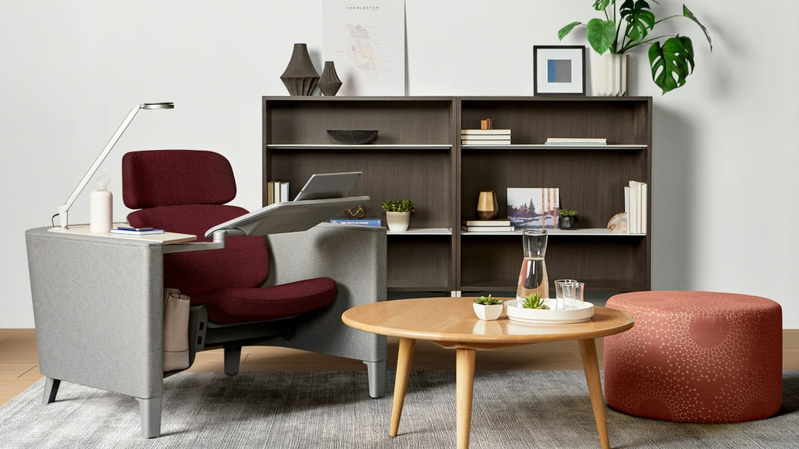 Private room with a red Brody seat with a Dash light and personal table, a laptop on it. A wooden coffee table with a water vase on it. A wooden storage behind with a plant above it.