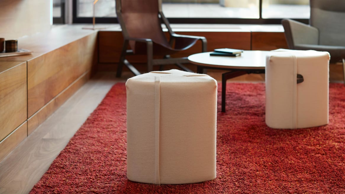 Two taupe Campfire Poufs pictured with a Bassline table, CH445 Wing chair, and Blu Dot Toro lounge chair