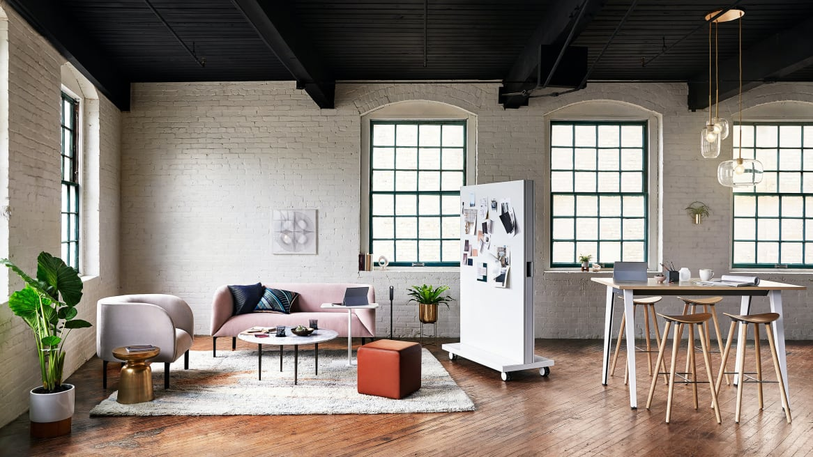 An Exponents mobile whiteboard separates two collaborative spaces. On the left is a pink Billow low back sofa and a beige Billow lounge chair from West Elm and on the right is a Steelcase B-Free table with four Enea Cafe Wood Stools from Coalesse.