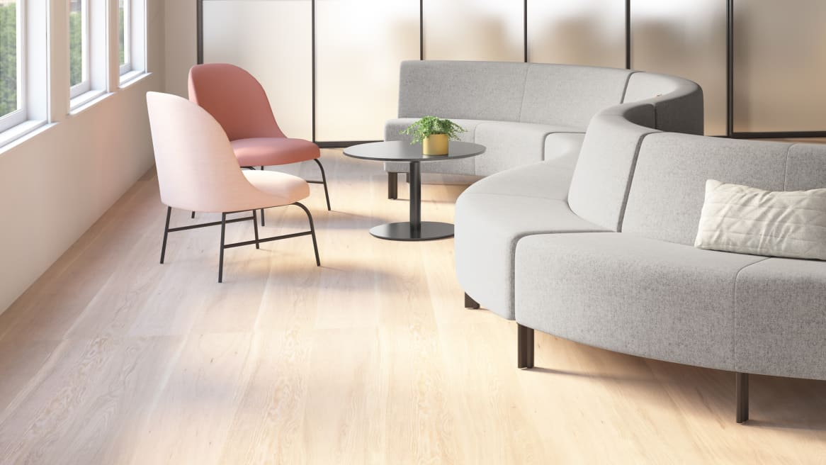 A Circa lounge seating system from Coalesse with gray upholstery with two pink chairs and a round gray table nearby
