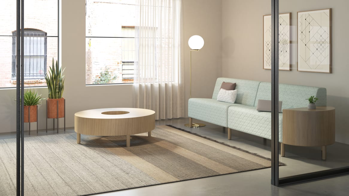 Circa lounge system with light green upholstery and a Circa round table in a wood veneer