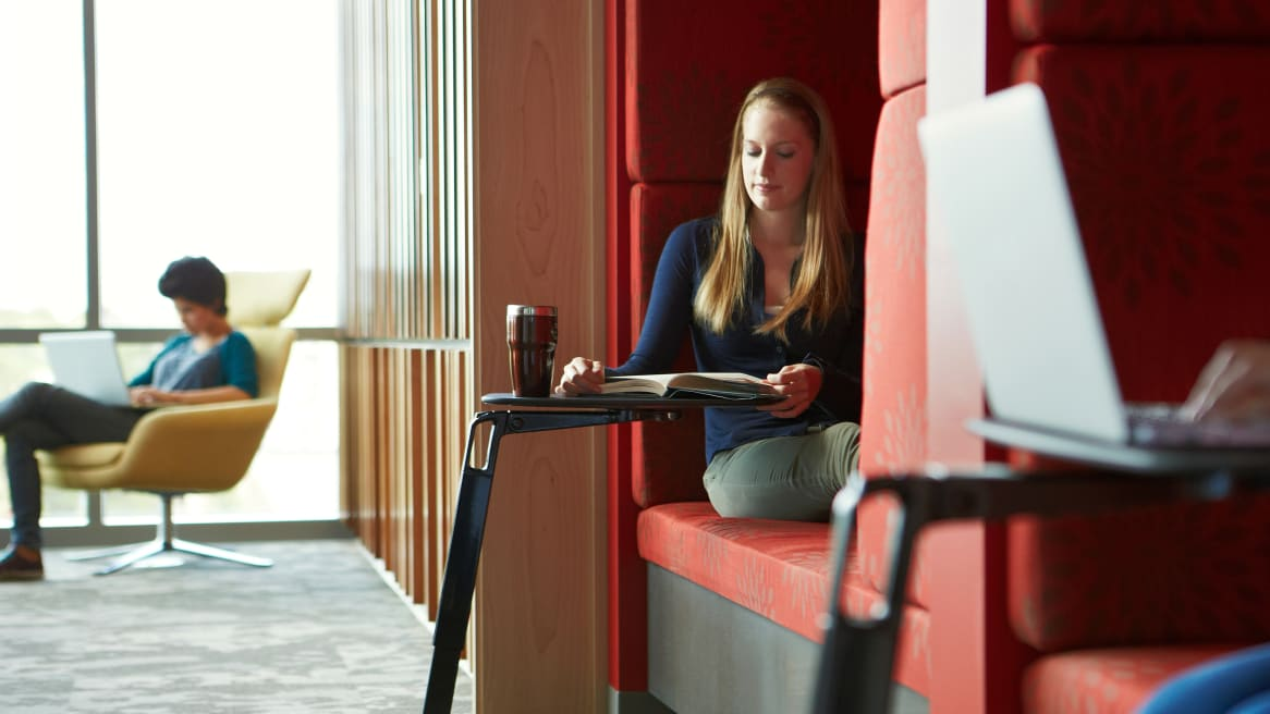 A woman reading a book while she sits on a red lounge booth with a personal table.