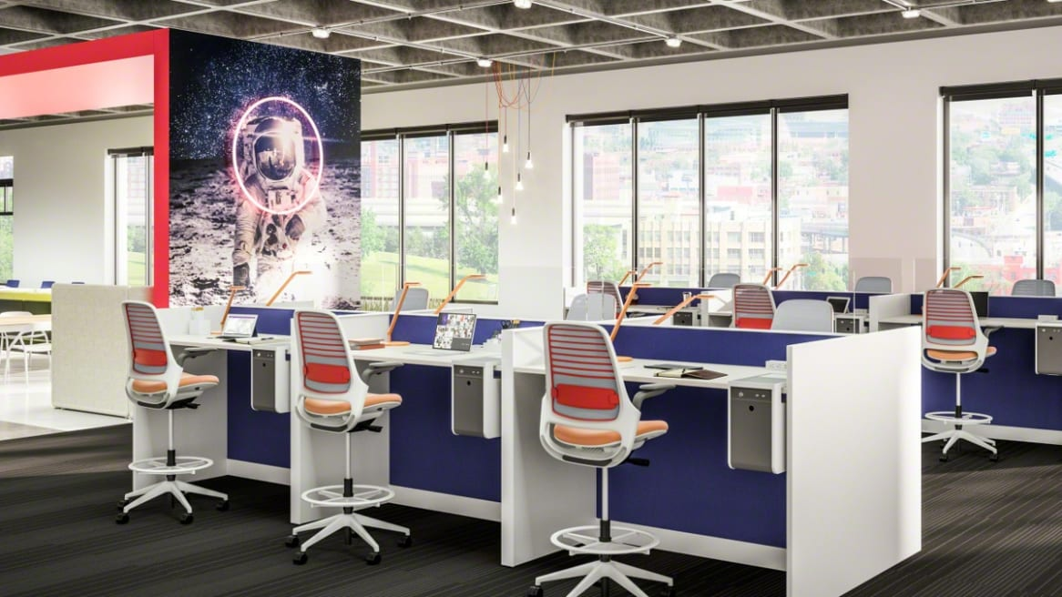 Workstations in an office space are created using Steelcase Series 1 task chairs with orange upholstery contrasting against blue Answer panel systems from Steelcase