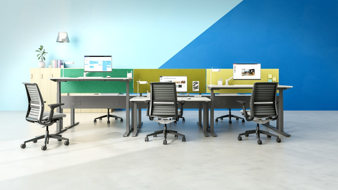 A group of workstations featuring Migration SE height-adjustable desks, Universal privacy screens, and Think desk chairs