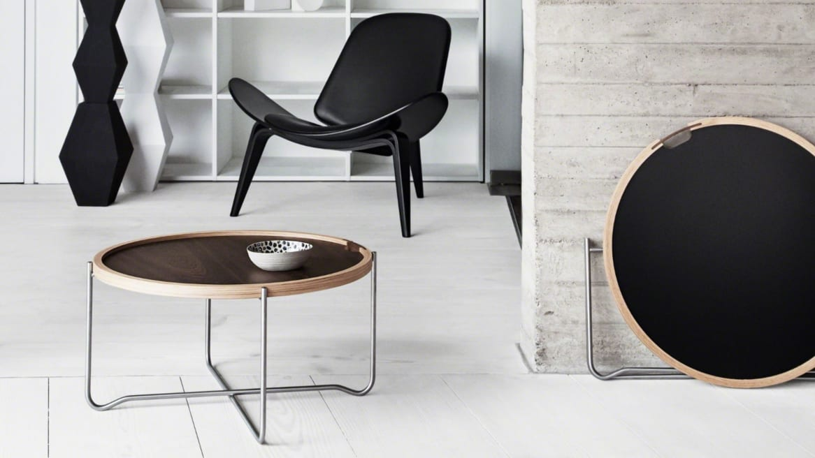 A CH417 Tray table by Carl Hansen & Son with a dark wood top is in the foreground with a black Shell chair in the background
