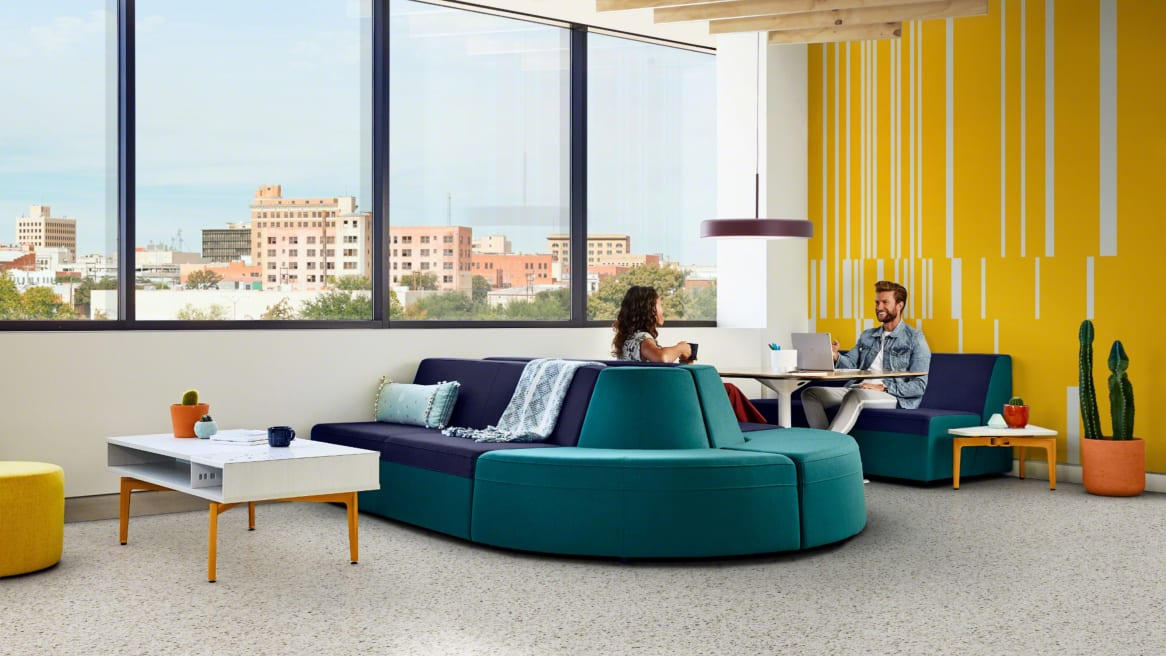 Two people have a conversation while working in a lounge area with a Campfire Lounge System, a Bassline Box Top coffee table, and a Bassline Asymmetric side table